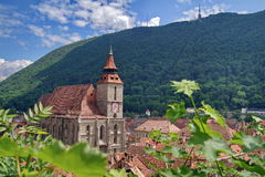 Landmark attraction in Brasov, Romania. Old town. The catholic Black Church (Biserica Neagra) and Tampa mountains