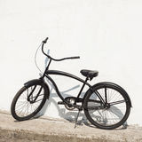 Black city bicycle cruiser standing by next white wall Stock Image
