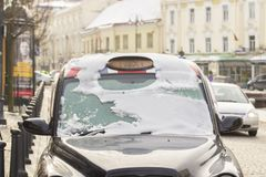 Black city taxi cab in snow. Old town of Vilnius, Lithuania stock photo