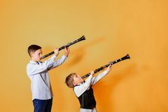 Black clarinet on an orange background in the hands of young performers of the folk mazy. Two brothers with clarinets, performing. At a musical concert stock images