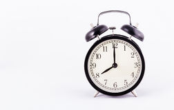 Black classic alarm clock on a white background. Black watch. Copy space stock photography
