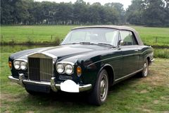 Black classic car. Black cabriolet type Rolls Royce classic car with soft top in a meadow with trees in the background royalty free stock photography
