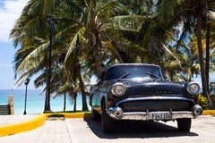 A black classic car parked near the beach Royalty Free Stock Image