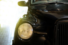 A black classic car. A black classic car with yellow light added as background Stock Image