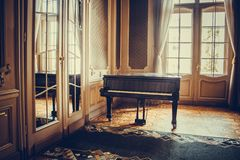 A black classic grand piano stands in the middle of a luxury room next to a window under sunlight. classical musical instrument, royalty free stock images