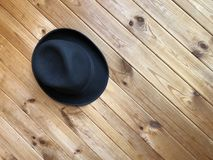 Felt black hat on a wooden background. Black classic hat hanging on a wooden wall. Diagonal wooden boards. Felt black hat on a wooden background. Blogger royalty free stock images