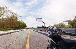Black classic motorcycle on the long way road under sunny sky Royalty Free Stock Photo