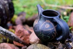 Black clay jug and old wooden barrel on stone pile.  royalty free stock image