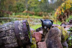 Black clay jug and old wooden barrel on stone pile.  royalty free stock photo