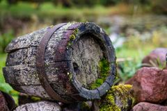 Black clay jug and old wooden barrel on stone pile.  stock photography