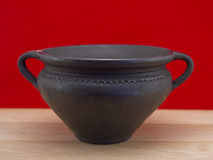 Black clay pot against red background Royalty Free Stock Photo