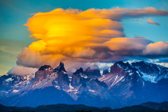 The black the cliffs of Los Cuernos. Magnificent orange clouds in the rays of the sunset. The black cliffs of Los Cuernos. The concept of extreme and active royalty free stock photo