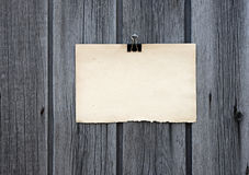 Black clip and old blank note paper hang. On wood panel royalty free stock images