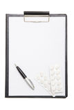 Black clipboard with blank paper sheet, pen and pills isolated o Royalty Free Stock Photography
