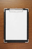 Black clipboard with paper on wooden table. A clipboard holding white paper Stock Image