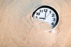 Black clock. In beach sand Royalty Free Stock Images