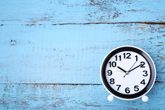Black clock. On blue wooden table Stock Photography