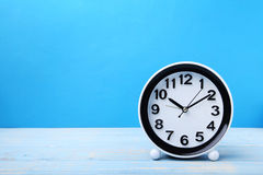 Black clock. On blue wooden table Royalty Free Stock Images