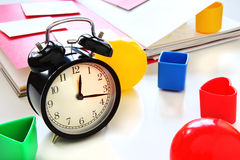 Black Clock with Colorful Toys with Open Red Book as Background. Royalty Free Stock Images