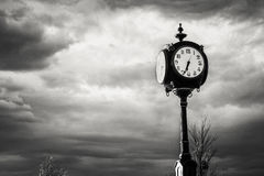 Black Clock at the Crossroads Against a Stormy Sky Royalty Free Stock Image