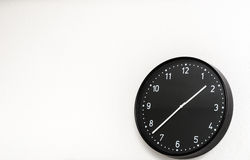 Black clock on wall. Modern black clock on white wall Stock Images