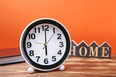 Black clock. With notebook on brown wooden table Royalty Free Stock Photo