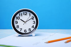 Black clock. With notebook and pencil on blue wooden table Royalty Free Stock Photo