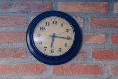 The black clock is on the old brick wall stock photography