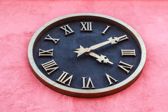 A black clock. On the pink wall Royalty Free Stock Photography