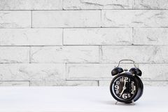 Black clock on white table and wall background Stock Photo