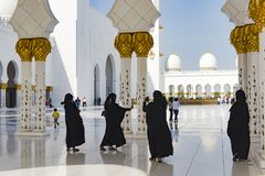 Black clothed women in hijab taking selfies in great mosque, Sheikh Zayed Grand Mosque, Abu Dhabi stock photos