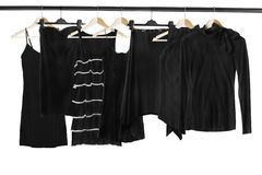 Black clothes on clothes racks. Set of black clothes on wooden clothes racks isolated over white Stock Images