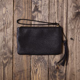 Black clutch bag. On a wooden floor Stock Photography