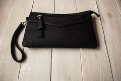 Black clutch on wooden background stock image