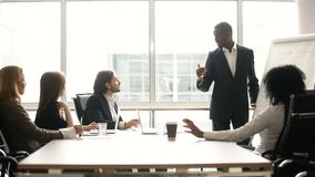 Black coach giving presentation for businesspeople in office with flipchart. African american coach gives corporate presentation for businesspeople in office stock footage
