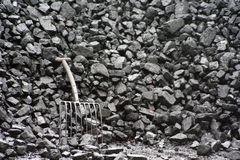 Black coal. A stack of coal with a coal fork to the left side Royalty Free Stock Image