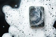 Black coal bar of soap in foam on dark Stock Image