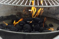 Black coal briquettes on fire under bbq mesh Royalty Free Stock Image