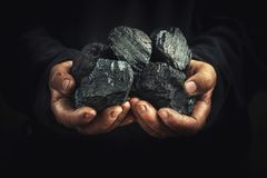 Black coal in the hands, heavy industry, heating. Mineral raw materials stock images