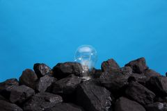 Black coal with a lighted bulb on top on a blue background. Coal as the basis of energy for electricity and heat. Black rock. Coal. Fossil fuel. Fuel with a royalty free stock photography
