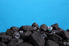 Black coal is strewn on a prism on a blue background and among it there are polished diamonds. royalty free stock photos