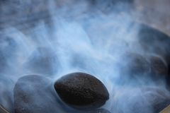 Black coals in white smoke. In the grill stock photography