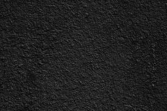 Black coarse surface of plastered concrete - dark background. Coarse surface of plastered concrete wall. Black rough cement texture. Dark background royalty free stock image