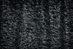 Black coarse textured old cement plaster dappled wall background. Black coarse textured old cement plaster. Dark dappled wall background royalty free stock photos
