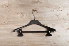 Black coat hanger on wooden background stock photo