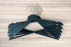 Black coat hangers on the wooden background Stock Photo