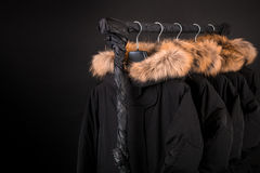 Black coats, jacket with fur on hood hanging  clothes rack.  background. Copy space. Royalty Free Stock Images