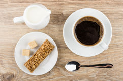 Black coffe in cup, jug of milk, granola bar. And lumpy sugar on wooden table. Top view Royalty Free Stock Images