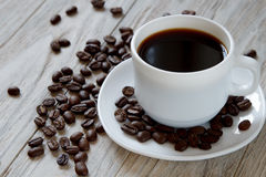 Black coffe and roasted beans in a white mug on wooden surface Royalty Free Stock Photo