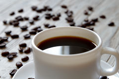 Black coffe in a white cup and scattered roasted beans on wooden surface Stock Images